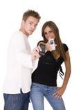 Pares sonrientes con los teléfonos Foto de archivo libre de regalías