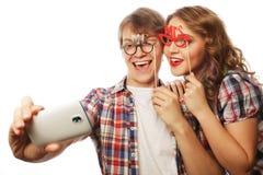Pares sonrientes con smartphone, el selfie y la diversión Fotos de archivo libres de regalías