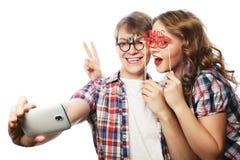 Pares sonrientes con smartphone, el selfie y la diversión Imagen de archivo