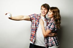 Pares sonrientes con smartphone, el selfie y la diversión Fotografía de archivo