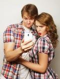 Pares sonrientes con smartphone, el selfie y la diversión Fotografía de archivo libre de regalías