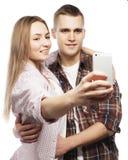 Pares sonrientes con smartphone, el selfie y la diversión Imagenes de archivo