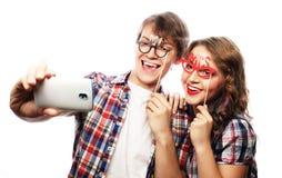 Pares sonrientes con smartphone, el selfie y la diversión Imágenes de archivo libres de regalías