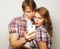 Pares sonrientes con smartphone, el selfie y la diversión Foto de archivo