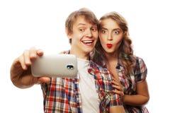 Pares sonrientes con smartphone, el selfie y la diversión Fotos de archivo