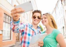 Pares sonrientes con smartphone en ciudad Imagen de archivo libre de regalías
