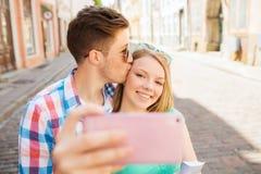 Pares sonrientes con smartphone en ciudad Fotos de archivo