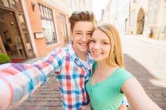 Pares sonrientes con smartphone en ciudad Imagenes de archivo