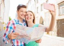 Pares sonrientes con smartphone en ciudad Foto de archivo libre de regalías