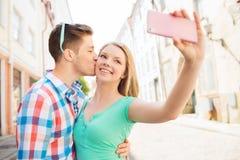 Pares sonrientes con smartphone en ciudad Fotos de archivo libres de regalías