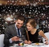Pares sonrientes con smartphone en el restaurante Imagenes de archivo