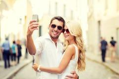 Pares sonrientes con smartphone en la ciudad Fotos de archivo libres de regalías