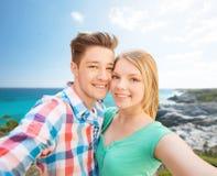Pares sonrientes con smartphone en la playa del verano Foto de archivo