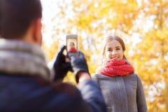 Pares sonrientes con smartphone en parque del otoño Imagenes de archivo