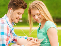 Pares sonrientes con smartphone y los auriculares Foto de archivo libre de regalías