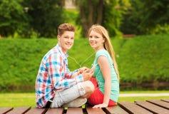 Pares sonrientes con smartphone y los auriculares Imagen de archivo libre de regalías