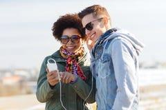Pares sonrientes con smartphone y los auriculares Foto de archivo
