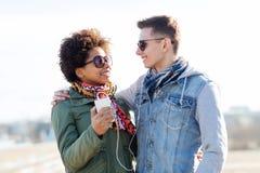 Pares sonrientes con smartphone y los auriculares Fotos de archivo libres de regalías
