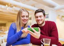 Pares sonrientes con té de consumición del smartphone Imagenes de archivo