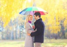 Pares sonrientes de amor felices con el paraguas colorido en soleado caliente imagen de archivo
