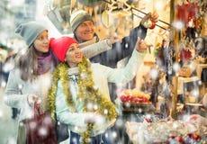 Pares sonrientes de la familia con la muchacha adolescente que elige decorati de la Navidad Fotografía de archivo libre de regalías