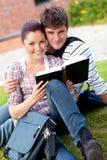 Pares sonrientes de los estudiantes que leen un libro Imagen de archivo libre de regalías