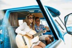 Pares sonrientes del hippie con la guitarra en coche del minivan Foto de archivo libre de regalías