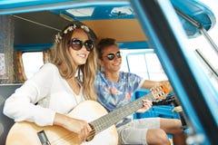 Pares sonrientes del hippie con la guitarra en coche del minivan Imagen de archivo libre de regalías