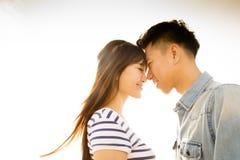Pares sonrientes en amor con el fondo de la luz del sol Imágenes de archivo libres de regalías