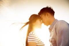 Pares sonrientes en amor con el fondo de la luz del sol Imagen de archivo