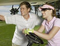 Pares sonrientes en carro de golf Imagen de archivo