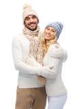 Pares sonrientes en el abrazo de la ropa del invierno Imagenes de archivo