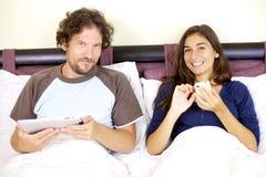 Pares sonrientes felices en cama con la tablilla y el teléfono Imagenes de archivo