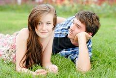 Pares sonrientes felices jovenes que mienten al aire libre Imagen de archivo