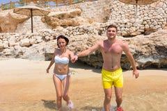 Pares sonrientes felices que corren en la playa que lleva a cabo las manos en un sol Fotos de archivo