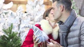 Pares sonrientes felices que hacen compras de la Navidad en tienda del mercado almacen de metraje de vídeo