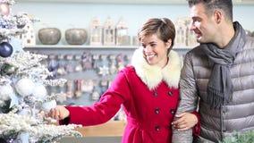 Pares sonrientes felices que hacen compras de la Navidad en tienda del mercado almacen de video