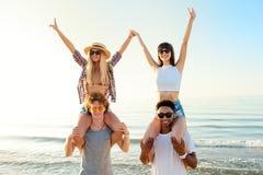 Pares sonrientes felices que juegan en la playa foto de archivo