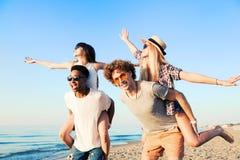 Pares sonrientes felices que juegan en la playa fotos de archivo