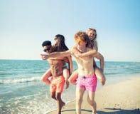 Pares sonrientes felices que juegan en la playa fotos de archivo libres de regalías