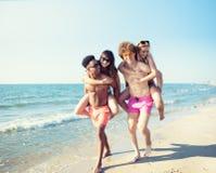 Pares sonrientes felices que juegan en la playa fotografía de archivo libre de regalías