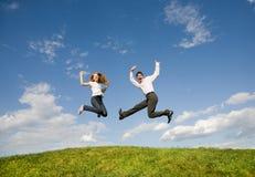 Pares sonrientes felices que saltan en cielo azul fotos de archivo