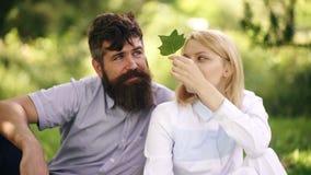 Pares sonrientes felices que se relajan en hierba verde Parque Familia joven que miente en hierba al aire libre Atención sanitari metrajes