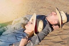 Pares sonrientes felices que se relajan en la arena, al aire libre Foto de archivo