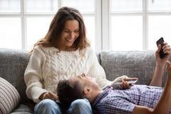 Pares sonrientes felices que se relajan en sostenerse de risa que habla del sofá Foto de archivo