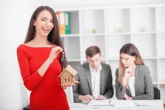 Pares sonrientes jovenes alrededor para firmar una casa que alquila el acuerdo, ha fotos de archivo libres de regalías