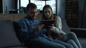 Pares sonrientes jovenes con la tableta que se relaja en el sofá almacen de video