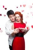 Pares sonrientes jovenes el día de tarjetas del día de San Valentín Imagen de archivo libre de regalías