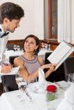 Pares sonrientes jovenes en el restaurante fotos de archivo libres de regalías