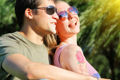 Pares sonrientes jovenes en las gafas de sol que se sientan en un parque en día soleado amistad, ocio, concepto del verano Fotos de archivo libres de regalías
